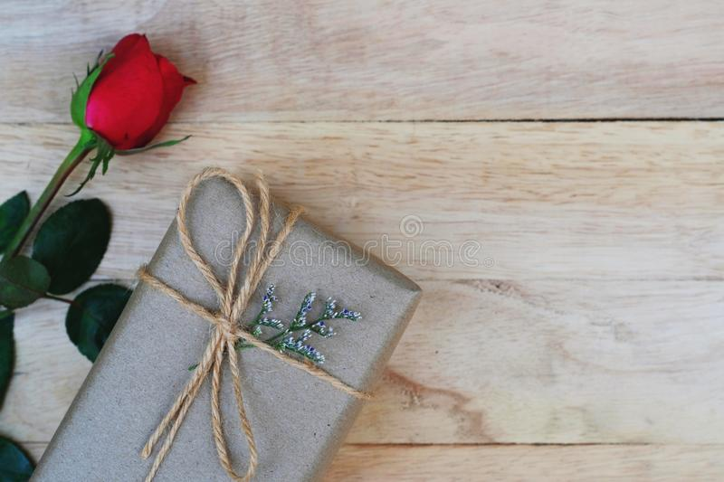 Eco friendly brown paper wrapped gift box present decorated with rose and other flowers on wooden background, valentine ornamental. Concept, copy space stock photos