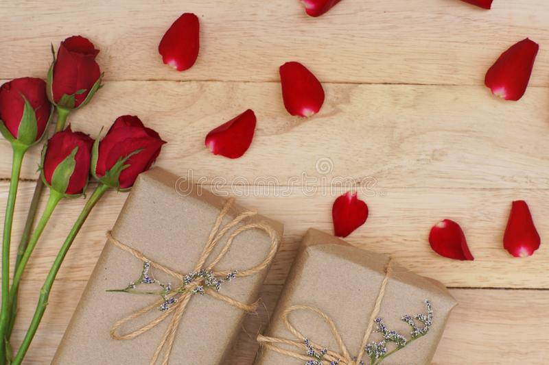 Eco friendly brown paper wrapped gift box present decorated with rose and other flowers on wooden background, valentine ornamental. Concept, copy space royalty free stock photography