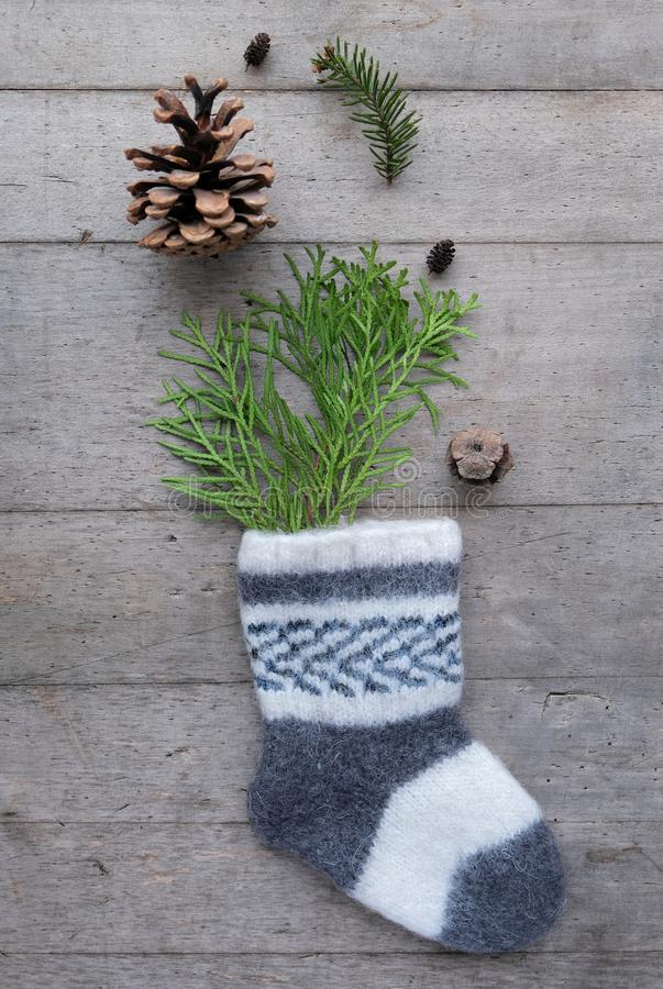 Eco Friendly Christmas flat lay. Winter holiday in Hygge style. Knitted childs socks with fir branches and cones. Coziness Xmas. Decoration on rustic wooden royalty free stock photo