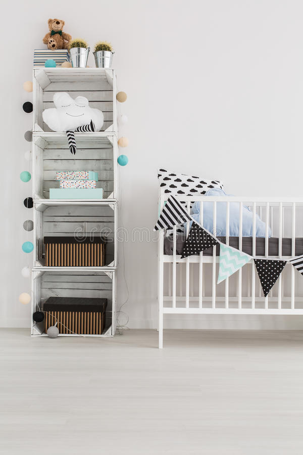 Eco-friendly design for big and small nature-lovers. Pallet rack with baby accessories and white crib in baby room royalty free stock photography