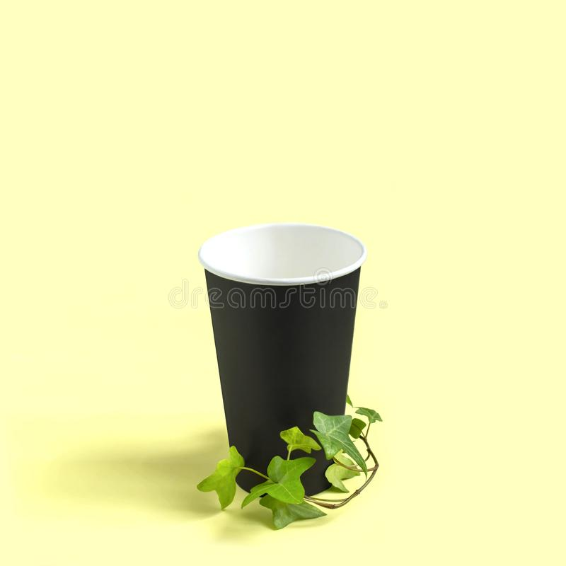 Eco-friendly disposable paper cup with green plant branch. Use paper disposable utensils instead of plastic, zero waste. Concept of social responsibility and royalty free stock photos
