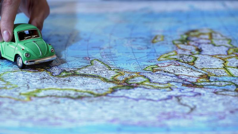 Eco friendly green car model driving across Europe on world map, travel by auto. Stock photo stock photography