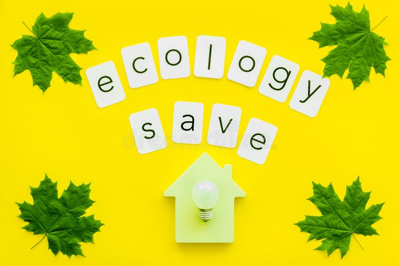 Green maple leaves, house figure, bulb and ecology save text for eco concept on yellow background top view. Eco friendly. Green maple leaves, house figure, bulb stock images