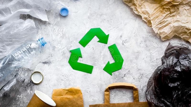 Eco-friendly life. Green paper recycling sign among waste paper, plastic, polyethylene on grey background top view.  stock photo