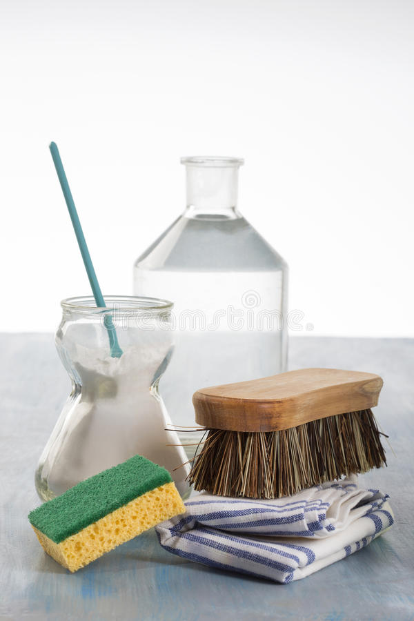Eco-friendly natural cleaners. Vinegar, baking soda, salt, lemon next to some clothes royalty free stock photos