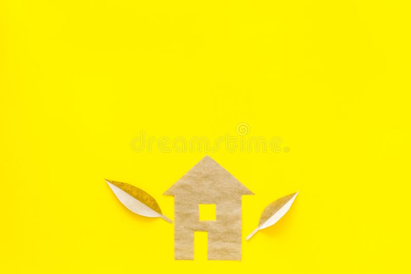 Eco friendly technologies for home concept. House silhouette made of craft paper on yellow background top view copy stock photo