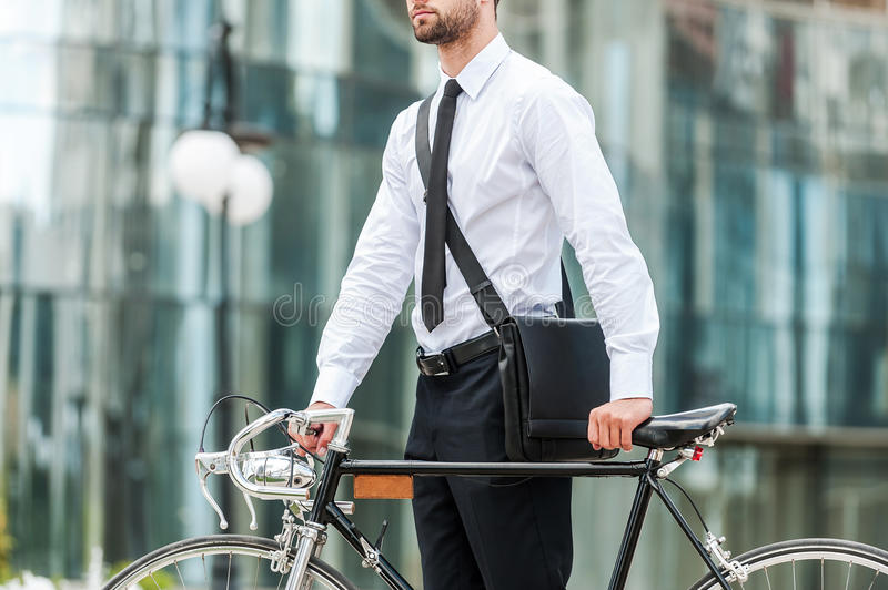 Eco-friendly way to get to work. Cropped image of young businessman holding hands on his bicycle while standing outdoors stock image