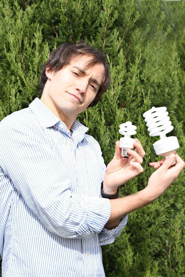 Eco-guy. Environmental series, man holding fluorescent lightbulb stock photos
