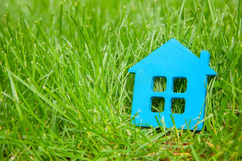 Eco house in nature. Symbol of house blue on green grass in summer. Copy space. For text stock photography