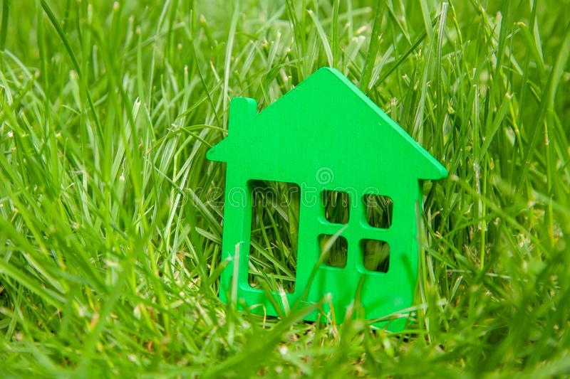 Eco house in nature. Symbol of house on green grass in summer.  stock photos