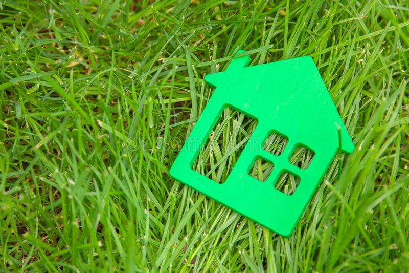 Eco house in nature. Symbol of house on green grass in summer. Copy space. For text stock photos