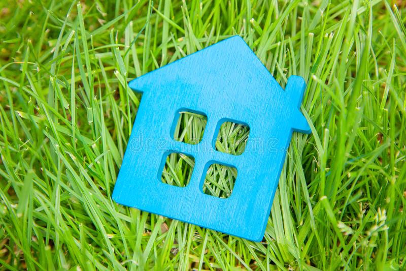 Eco house in nature. Symbol of house blue on grass in summer. Eco house in nature. Symbol of house blue on green grass in summer stock photography