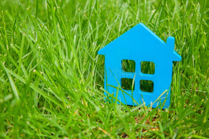 Eco house in nature. Symbol of house blue on green grass in summer. Copy space for text royalty free stock images