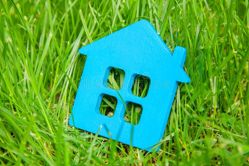 Eco house in nature. Symbol of house blue on green grass in summer.  stock photography