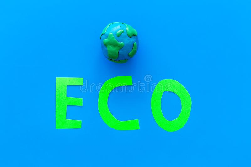 Eco icon cutout near planet Earth plastiline symbol on blue background top view copy space. Eco icon cutout near planet Earth plastiline symbol on blue stock photography