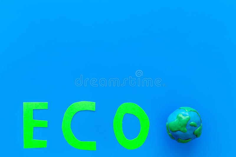 Eco icon cutout near planet Earth plastiline symbol on blue background top view space for text. Eco icon cutout near planet Earth plastiline symbol on blue stock photo