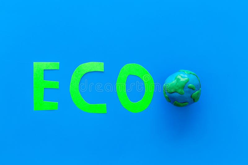 Eco icon cutout near planet Earth plastiline symbol on blue background top view space for text. Eco icon cutout near planet Earth plastiline symbol on blue stock image