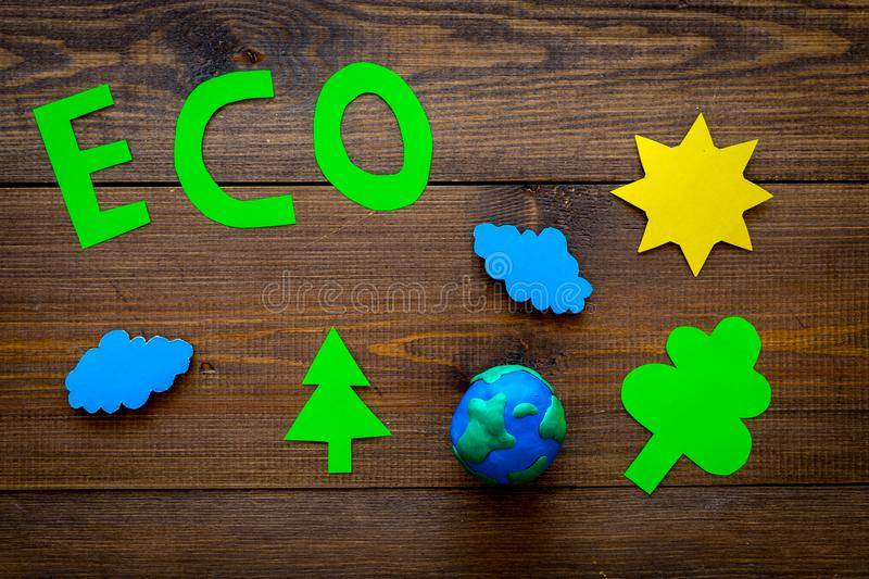 Eco icon cutout near plastiline symbol of planet Earth and environment as sun, trees, clouds on dark wooden background. Top view royalty free stock photo