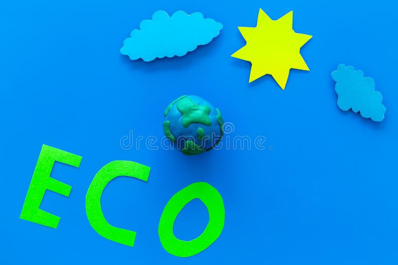 Eco icon cutout near plastiline symbol of planet Earth, sun, clouds on blue background top view copy space. Eco icon cutout near plastiline symbol of planet royalty free stock image