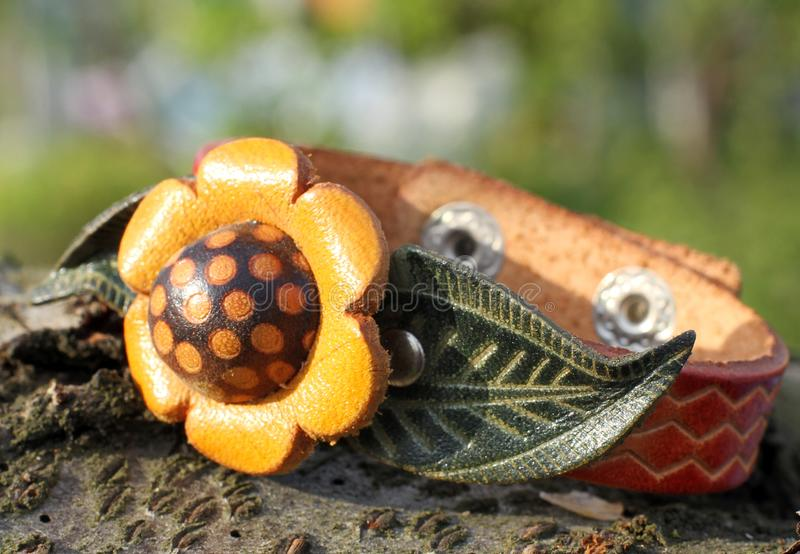 Eco leather bracelet with a flower hand made. Eco leather bracelet with a flower eco style hand made stock photography