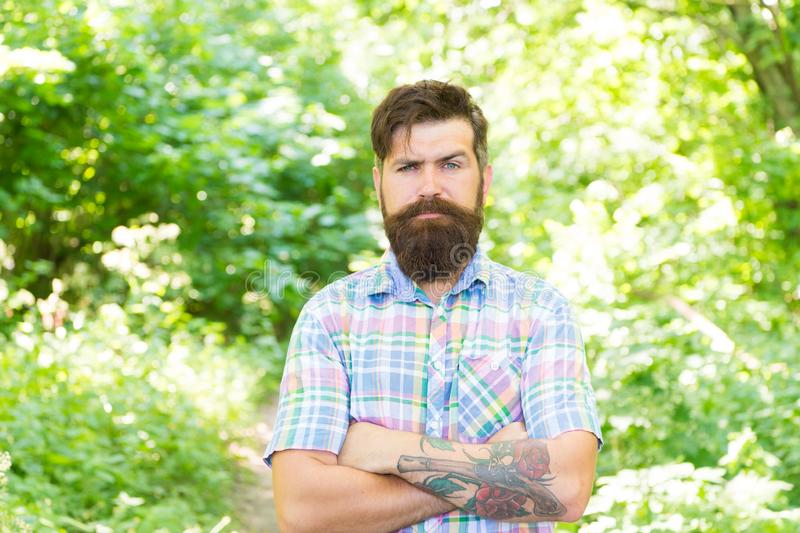 Eco lifestyle. United with environment. Handsome lumberjack. Man beard and mustache in summer forest. Summer vacation. Concept. Man bearded hipster green trees stock photography