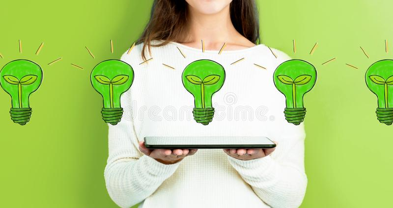 Eco light bulbs with woman holding a tablet royalty free stock photos