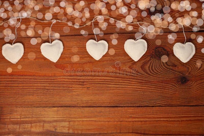 Eco-linnen stof harten op houten achtergrond, Valentijnsdagontwerp Decoratief wit hart op jute twine garland royalty-vrije stock fotografie