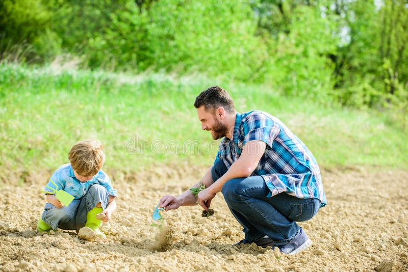 Eco living. happy earth day. Family tree. father and son planting flowers in ground. new life. soils fertilizers. rich. Natural soil. Eco farm. small boy help royalty free stock photo