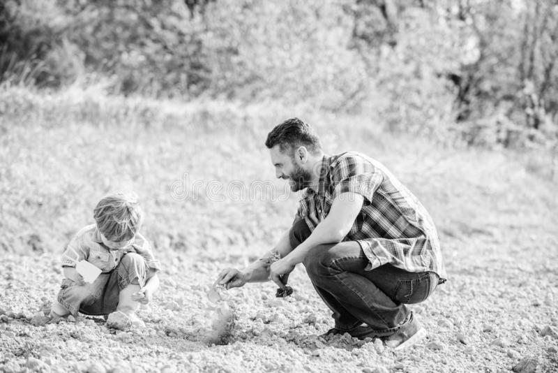 Eco living. happy earth day. Family tree. father and son planting flowers in ground. new life. soils fertilizers. rich. Natural soil. Eco farm. small boy help stock image
