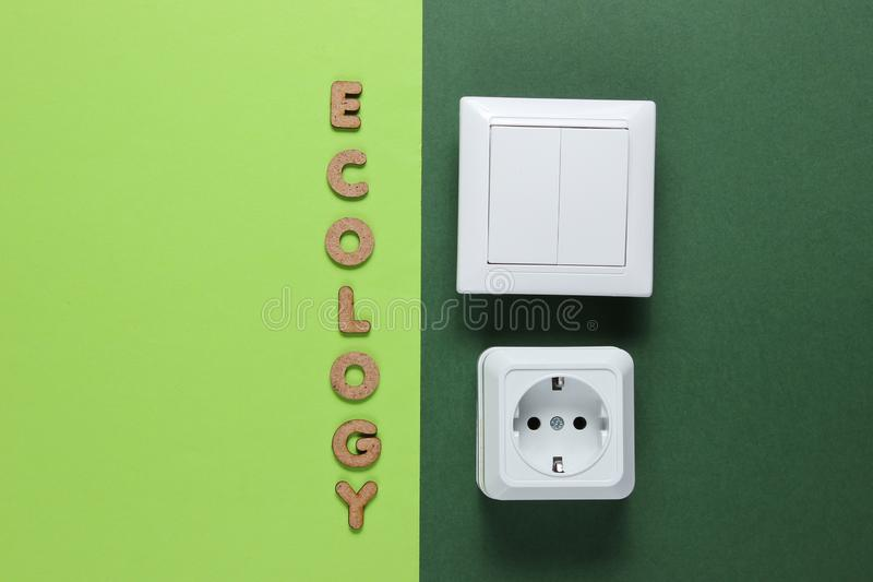 Eco. Power socket and switch with the word ecology on green background. Top view, inscription, wooden, letters, text, message, energy, efficiency, ecological stock photography