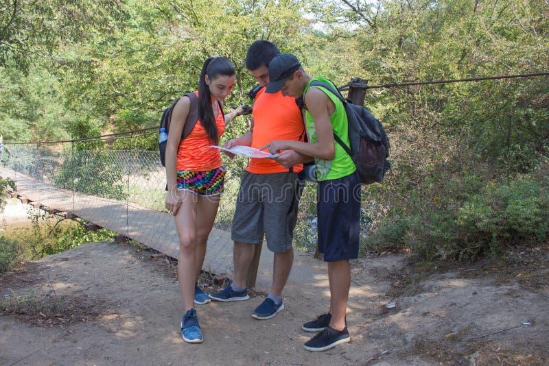 Eco turism och sunt livsstilbegrepp Unga pojkar för fotvandrareflickaslut med ryggsäcken Handelsresande fotvandrare på semester s royaltyfri bild