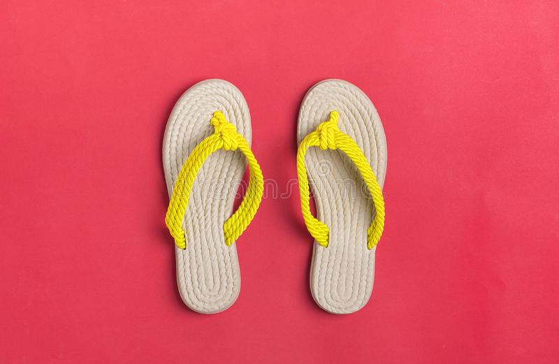 Eco yellow bamboo flip flops on red background Flat lay, top view. stock photos