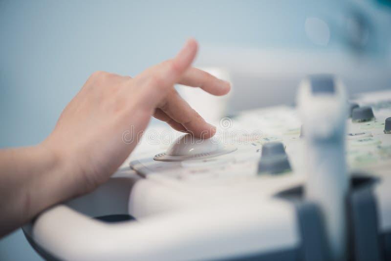 Ecografista abile facendo uso della macchina di ultrasuono sul lavoro immagine stock libera da diritti