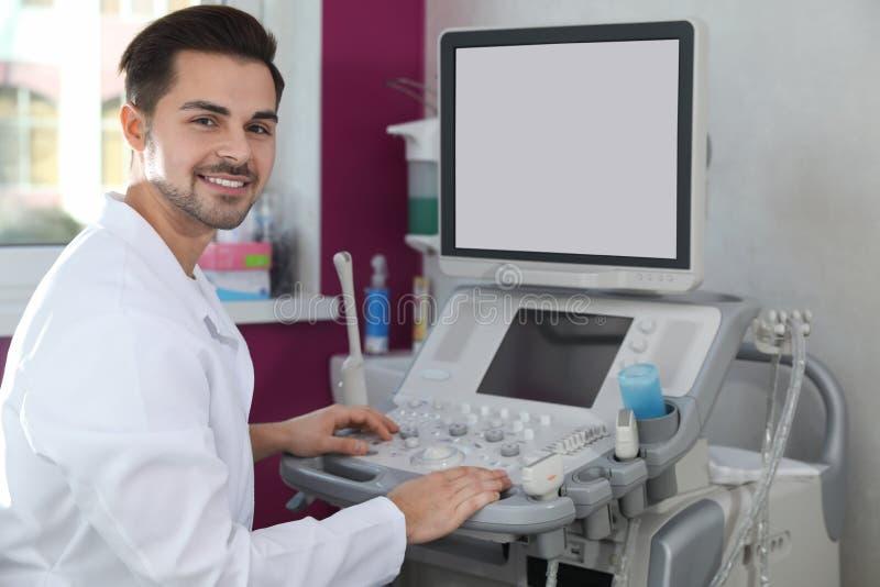 Ecografista facendo uso della macchina moderna di ultrasuono immagine stock libera da diritti