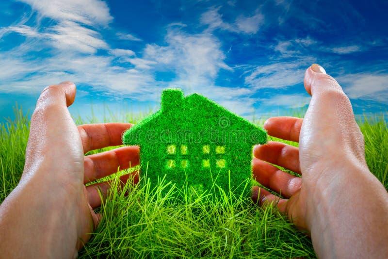 Ecohuis in groen die gras door de menselijke handen wordt beschermd stock fotografie