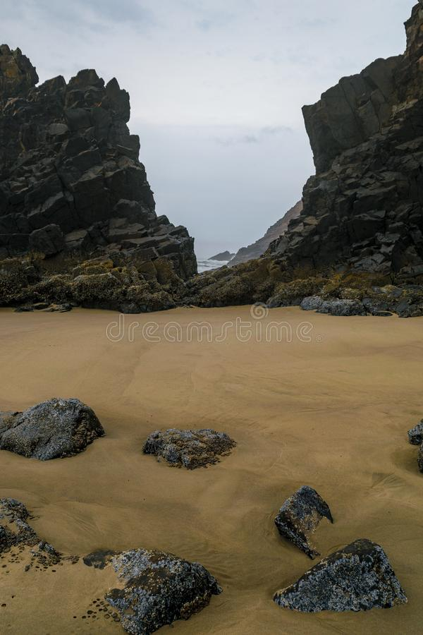 Ecola State Park - Indian Beach. Two rock formations along Indian Beach, Oregon, create a narrow pathway to a distant part of the beach. The light brown sand royalty free stock photos