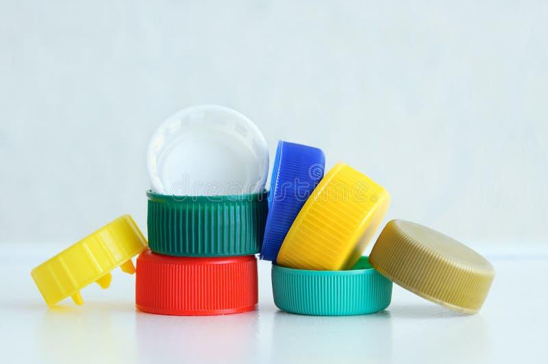 ecologia Di cappucci colorati multi di plastica per le bottiglie su un fondo grigio fotografia stock libera da diritti