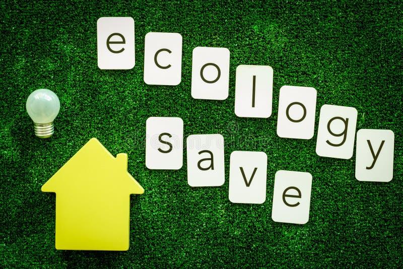 Ecologia salvo o texto e a casa com o bulbo para o conceito amigável do eco na opinião superior do fundo verde da textura fotos de stock royalty free