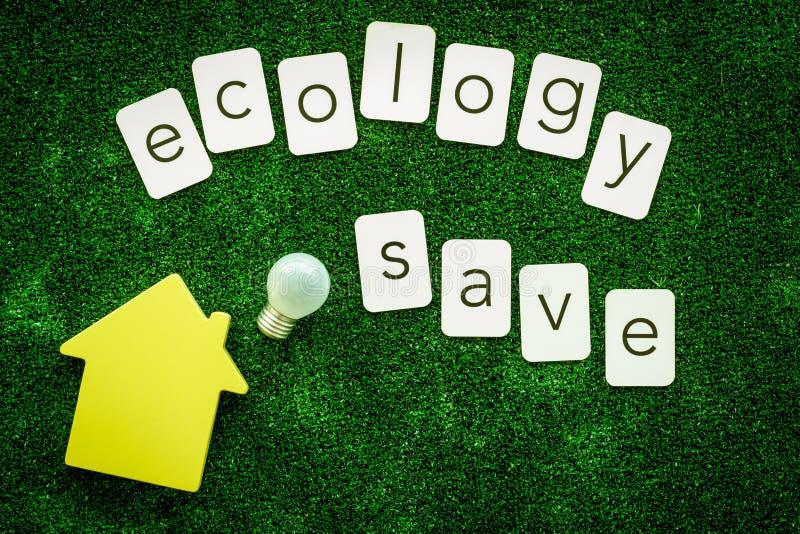 Ecologia salvo o texto e a casa com o bulbo para o conceito amigável do eco na opinião superior do fundo verde da textura fotografia de stock