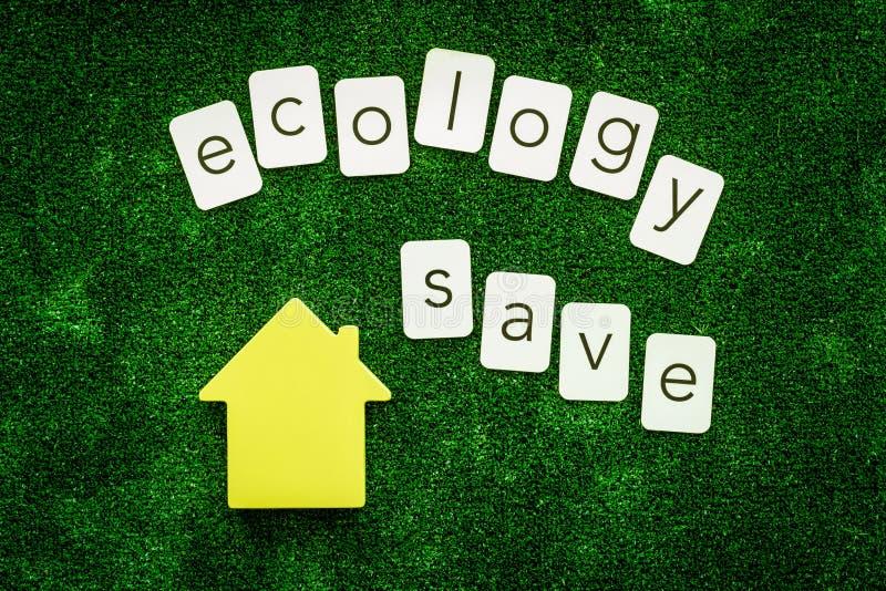 Ecologia salvo o texto e a casa para o conceito amigável do eco na opinião superior do fundo verde da textura imagem de stock