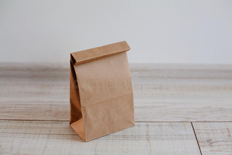 Ecologic craft package. Paper bag on light wooden floor. Simple brown paper bag for lunch or meal. The layout for the design. Environmental ship packages stock image