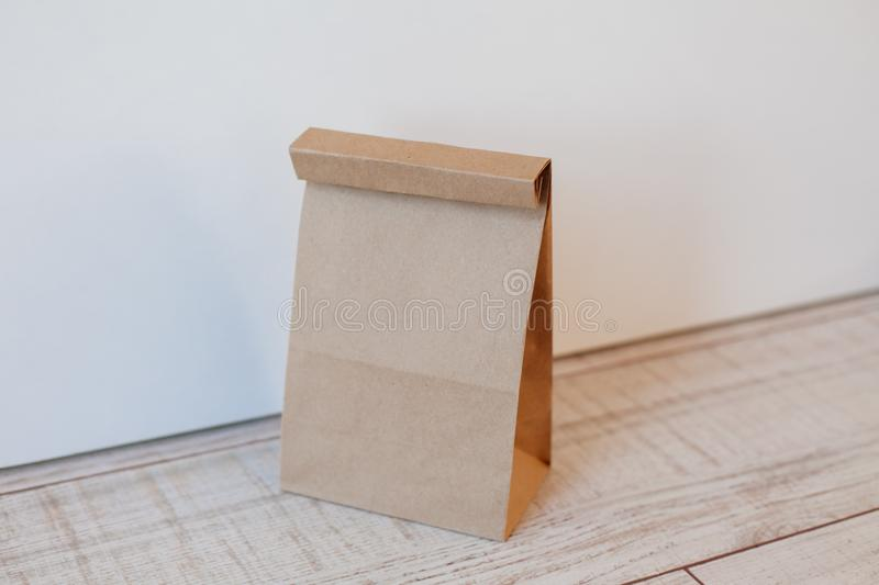 Ecologic craft package. Paper bag on light wooden floor. Simple brown paper bag for lunch or meal. The layout for the design. Environmental ship packages stock photos