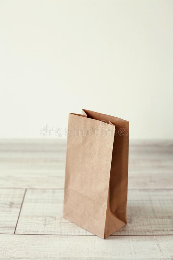 Ecologic craft package. Paper bag on light wooden floor. Simple brown paper bag for lunch or meal. The layout for the design. Environmental ship packages stock photo