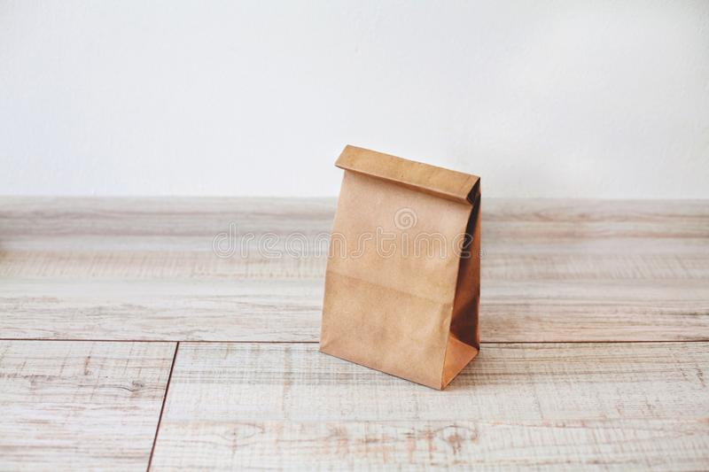 Ecologic craft package. Paper bag on light wooden floor. Simple brown paper bag for lunch or meal. The layout for the design. Environmental ship packages royalty free stock images
