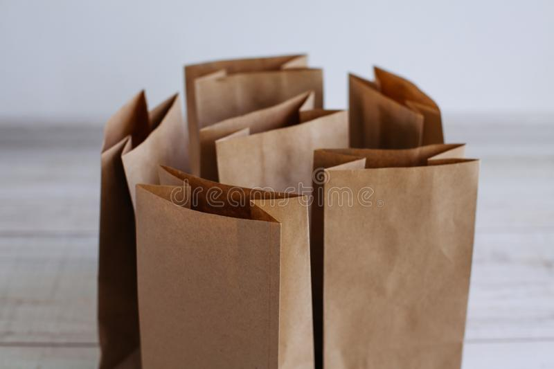 Ecologic craft package. Paper bags on light wooden floor. Simple brown paper bags for lunch or meal. The layout for the design. Environmental ship packages stock photo