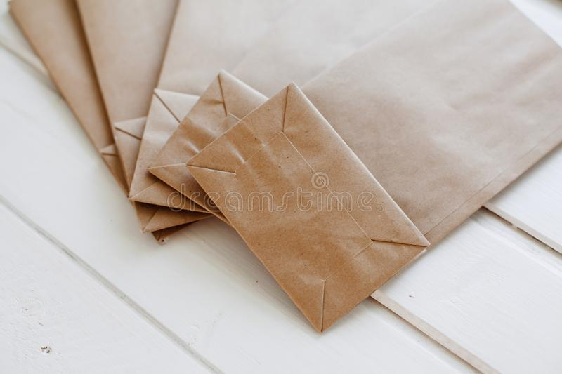 Ecologic craft package. Paper bags on light wooden floor. Simple brown paper bags for lunch or meal. The layout for the design. Environmental ship packages royalty free stock photography