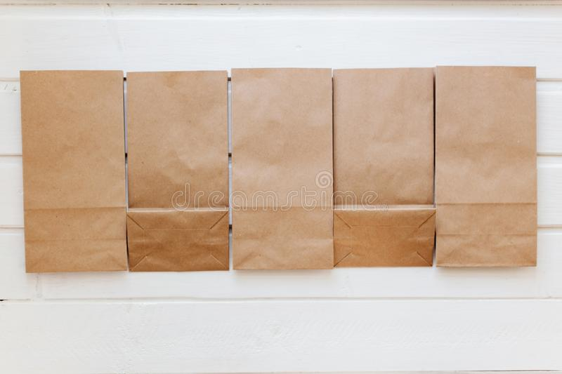 Ecologic craft package. Paper bags on light wooden floor. Simple brown paper bags for lunch or meal. The layout for the design. Environmental ship packages stock image