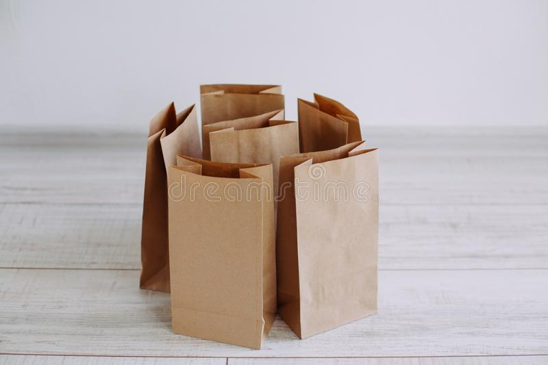 Ecologic craft package. Paper bags on light wooden floor. Simple brown paper bags for lunch or meal. The layout for the design. Environmental ship packages royalty free stock images