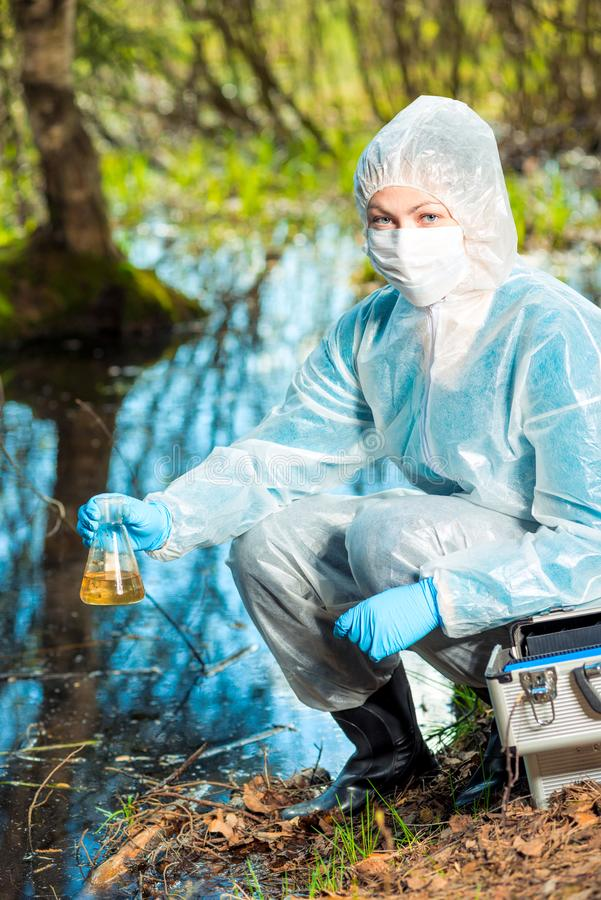 Ecological catastrophe - the ecologist is taking a sample of water in a flask from a forest. River royalty free stock photo