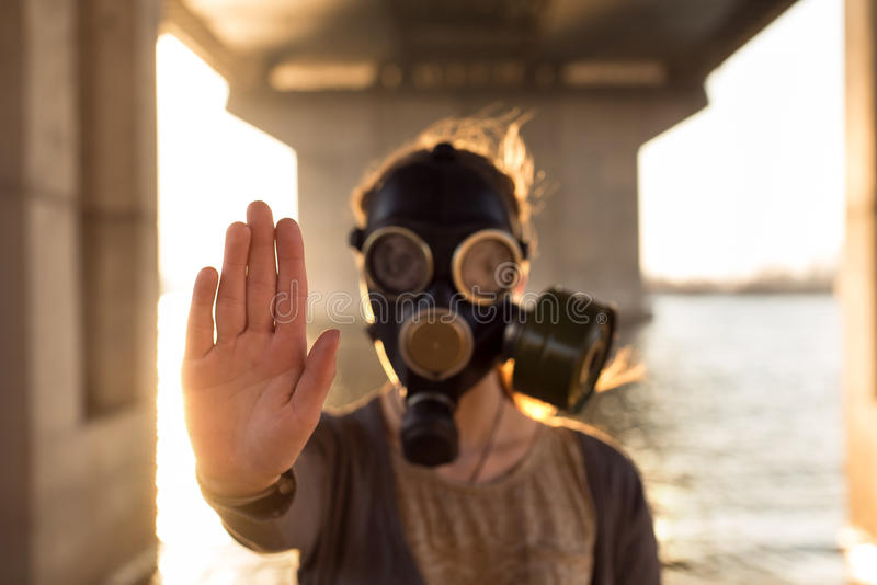 Ecological concept of air contamination. Woman in gas mask royalty free stock images